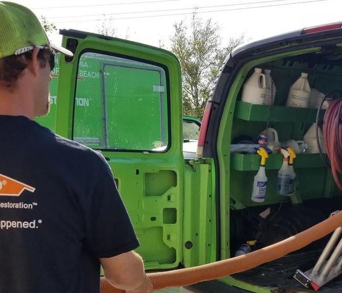 A male employee pulling a hose out of a SERVPRO van.