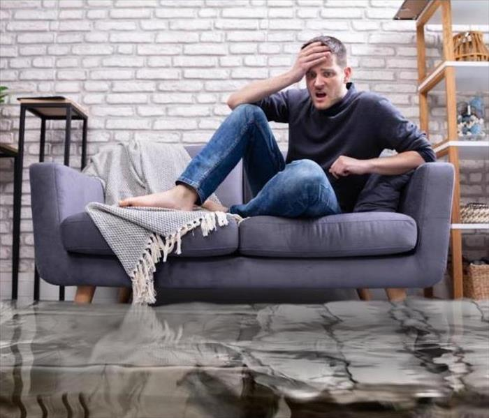 man on couch horrified by flood waters that surround him